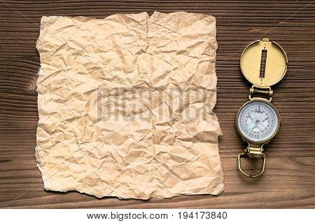 Compass and blank crumpled brown page paper on wooden table. Adventurer treasure hunt or travel concept.