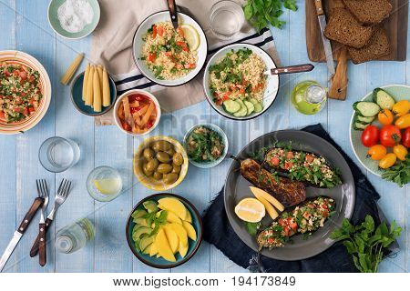 Set of healthy vegetarian food salad with bulgur porridge and vegetables stuffed eggplant vegetables mango avocado and snacks on a wooden table top view. Vegetarian food concept