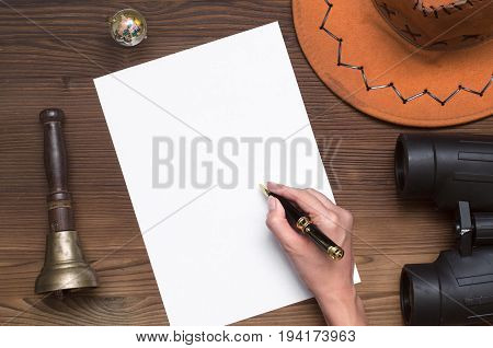 Adventurer treasure hunt travel concept or education mockup background. Hand with pen globe binoculars train conductor bell (teacher bell) hat and blank paper page on table.