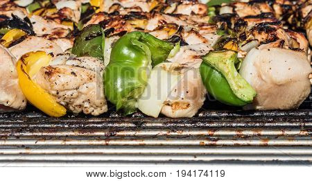 Chicken kabobs cooking on the grill close up
