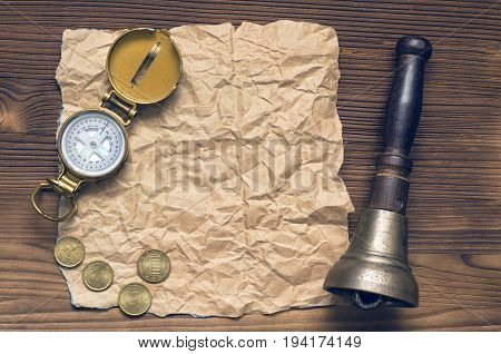 Compass train bell money and blank crumpled brown page paper on wooden table. Adventure treasure hunt journey or travel concept.