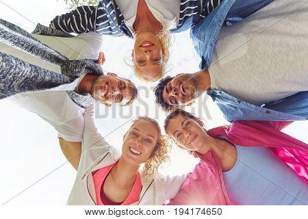 Team of teenagers in a group having fun in a hug
