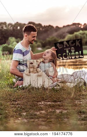 Happy father with cute daughter hard working in nature with the poster in hand back to school, education concept, family values