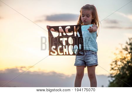 Sweet hard working girl in nature with a poster in hand back to school, education concept