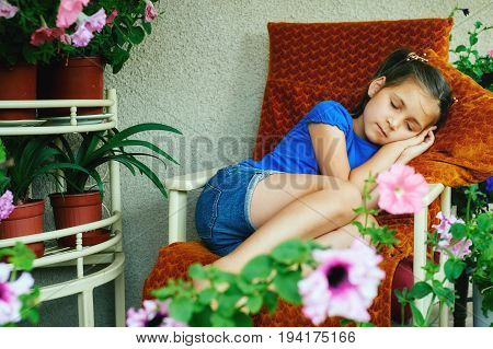 the little girl fell asleep in a chair on the porch on a summer day . Summer healthy sleep
