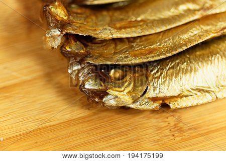 Smoked European sprats Sprattus sprattus on a wooden background.
