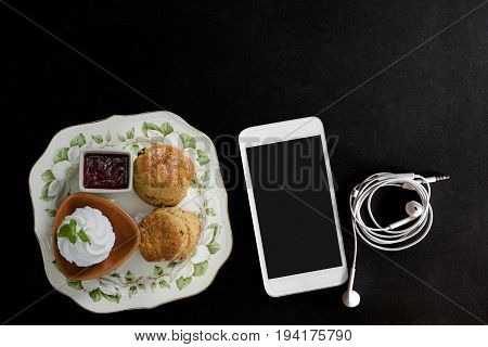 Traditional English cream tea of scones clotted cream strawberry jam and smartphone on dark table.