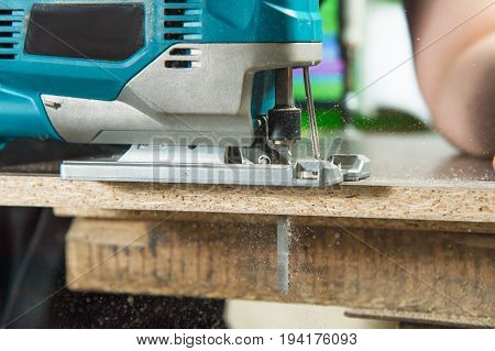 Close-up electric jigsaw for wood sawing a piece of wood and chips flying