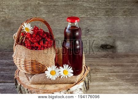 Viburnum berries in a basket on a napkin with daisies near the glass transparent bottle of juice. Rustic. Copy space. The horizontal frame.