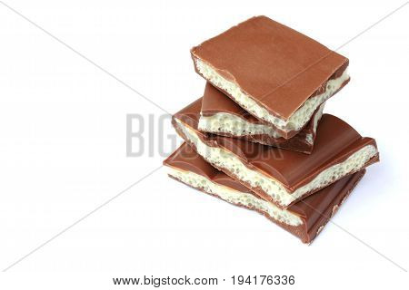 stack of pieces porous white and dark chocolate on white background closeup selective focus