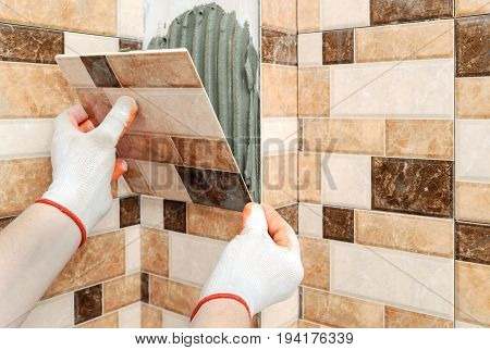 Installation of ceramic tiles. The tiler's hands are fixing the tile and forming Jolly Edge.