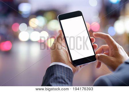 Smart phone showing blank screen in business man hand at walk street night light bokeh Background