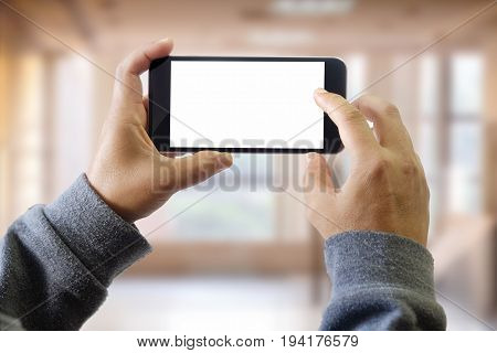 man using smart phone on window with city building background and copy space. Blank screen for graphic display montage.