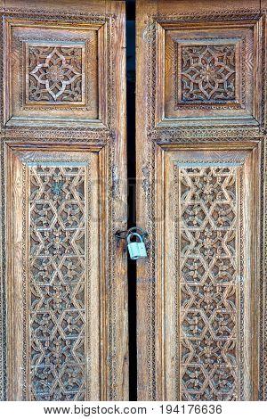 Old wooden carved door with the padlock. Uzbekistan