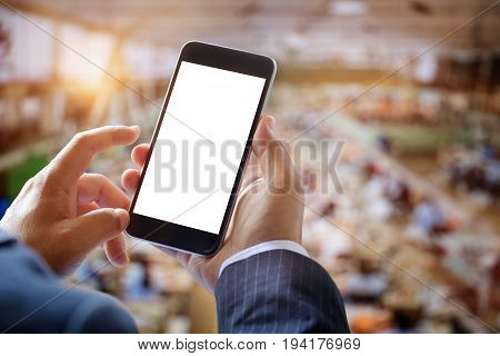 Businessman using smartphone in industrial size textile factory. Blank screen smartphone for graphic display montage.