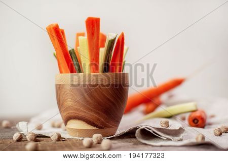 slices of fresh cut cucumbers and carrots in a wooden bowl