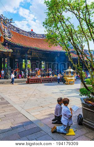 TAIPEI TAIWAN - JUNE 07: This is a temple scene of people praying at Longshan temple a popular buddhist temple in Taipei on June 07 2017 in Taipei