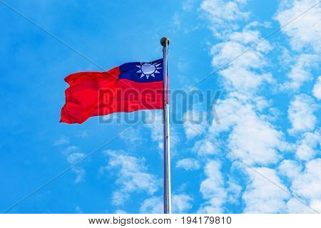 Taiwanese flag raised blowing in the wind with blue sky