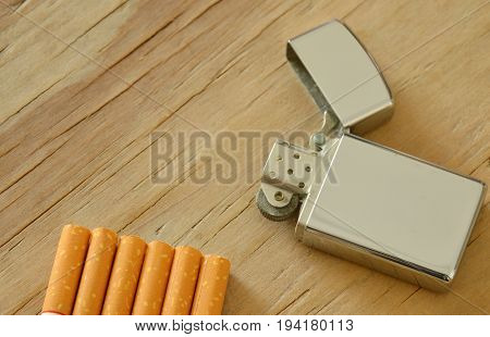 silver lighter with cigarette on wooden board