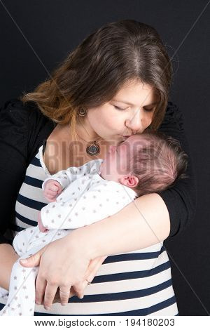 Young Mother Holding Her Newborn Child. Mom Nursing Baby. Woman And New Born Boy Relax