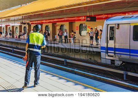 TAIPEI TAIWAN - MAY 29: This is an MRT station security officer ensuring that passenger board the trains safely which is common in MRT stations across the city on May 29 2017 in Taipei