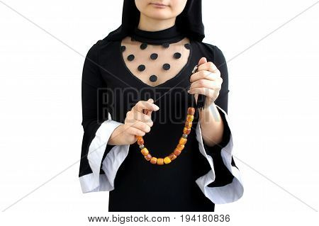 Female hands with rosary. Young woman in the clothes of a nun. Isolated on white background