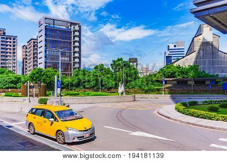 TAIPEI TAIWAN - MAY 29: This is a Taipei taxi waiting outside Guandu mrt station fior a passenger with modern city buildings in the background on May 29 2017 in Taipei
