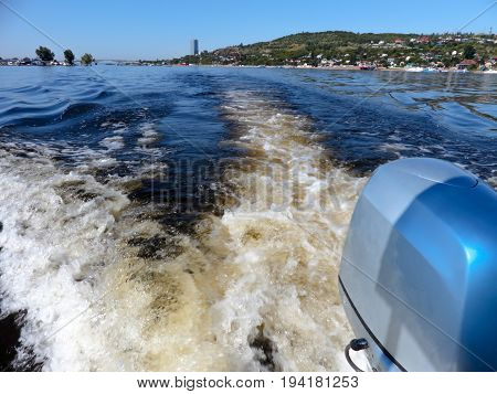 Outboard motor. Summer river landscape, photographed from the side of the boat. Russia, Saratov, the Volga river. Road bridge between the cities of Saratov and Engels.