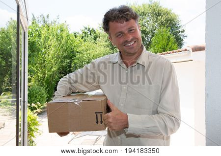Smiling Delivery Man Delivering Parcel Box To Recipient - Courier Service Concept