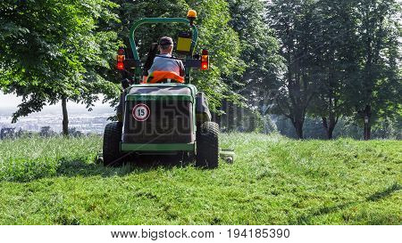Male using lawn mower and cutting grass. Around him a green landscape.
