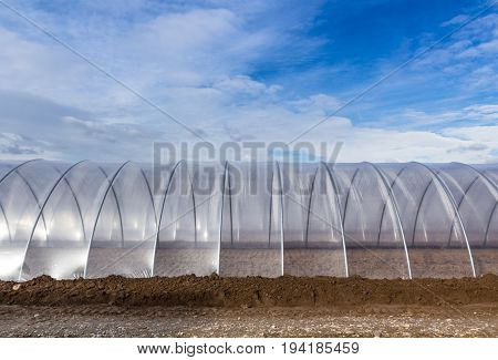 Greenhouse tunnel from polythene plastic on an agricultural field against the blue sky