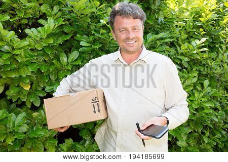 A Handsome Delivery Man Delivering A Package To House