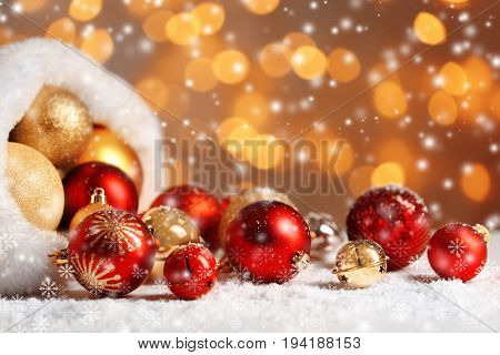 Santa hat with Christmas toys and snow effect on blurred lights background