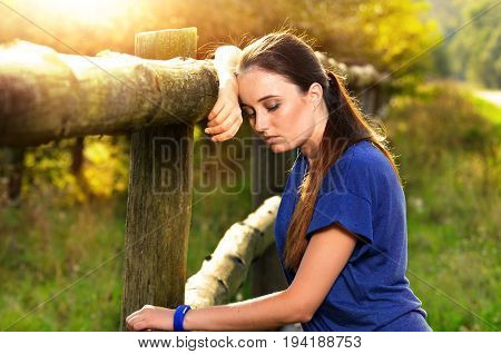 Woman Resting Near Fence After Jogging