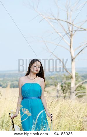 Young beautiful woman in dark cyan dress with white fiddle in her hands