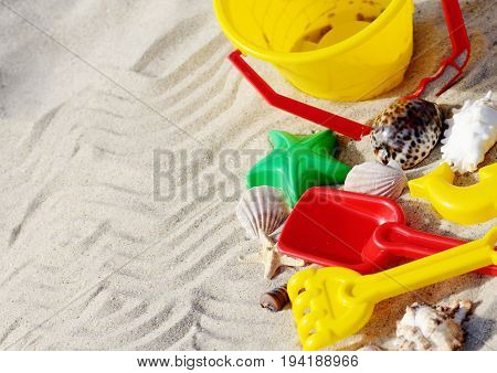 Bright plastic sandbox toys on the sand