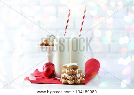 Glass bottles of milk with tasty gingerbread cookies and Christmas lights on blurred background