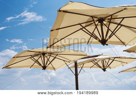 Large Parasols. Beach Season, Time Of Rest And Travel. Place For The Text. Blue Sky Background. Beac