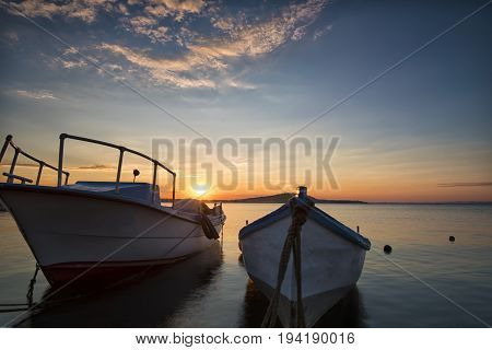 Two traditional wooden fishing boats in the sea. Fishing boats tied up in harbor at the end of the day. Sunset near the Black Sea coast