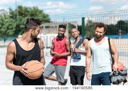 Multicultural Basketball Team Playing Basketball On Court In Summer