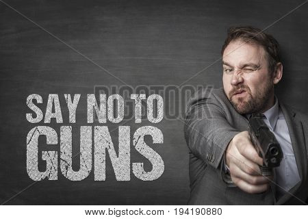Businessman aiming handgun while standing by say no to guns text on blackboard
