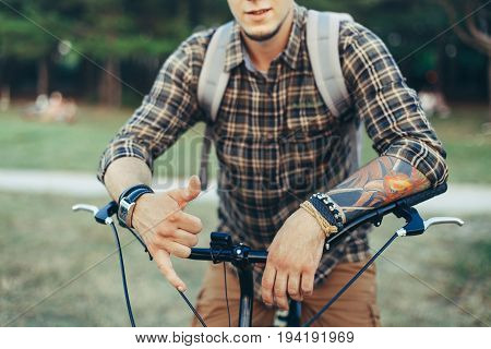 Young Man Shows A Hang Loose (Shaka Surfer) Sign By Hand Sitting On A Bicycle On Green Summer Meadow
