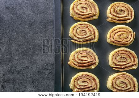 Raw cinnamon rolls on baking tray on kitchen table