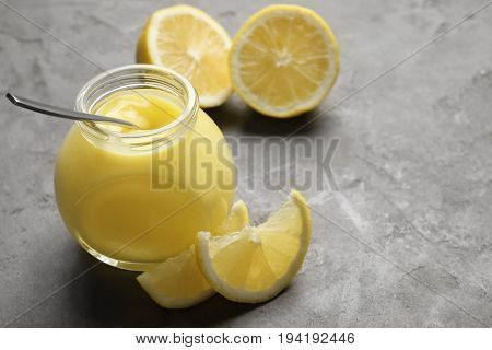 Glass jar with delicious lemon curd on gray table