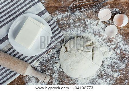 Top View Of Unbaked Dough With Ingredients And Rolling Pin On Table Top