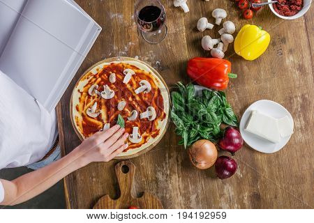 Top View Of Woman Holding Blank Cookbook While Preparing Pizza At Kitchen