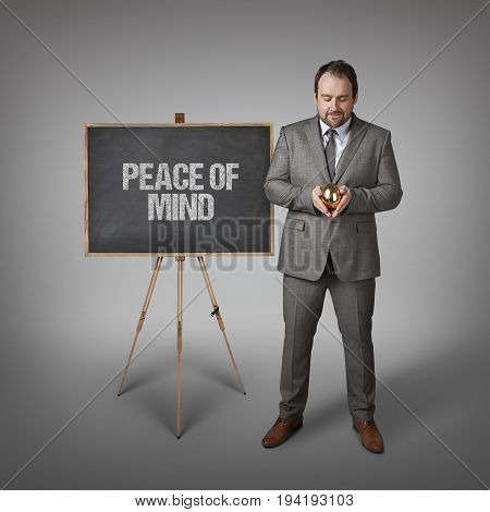 Peace of mind text on  blackboard with businessman and golden egg
