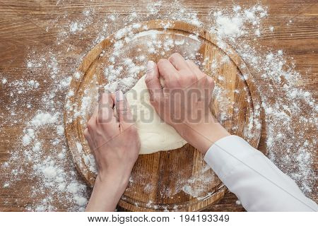 Cropped Shot Of Hands Kneading Dough On Wooden Board