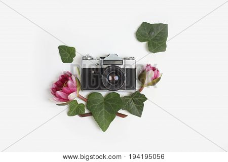 Vintage retro photo camera in the middle of floral frame made of green ivy leaves and nymphaea waterlily purple flowers on white background. Flat lay top view.