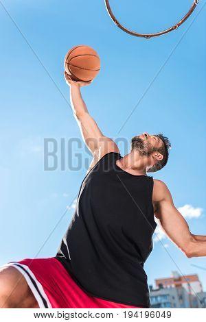 Low Angle View Of Basketball Player Throwing Ball Into Basket